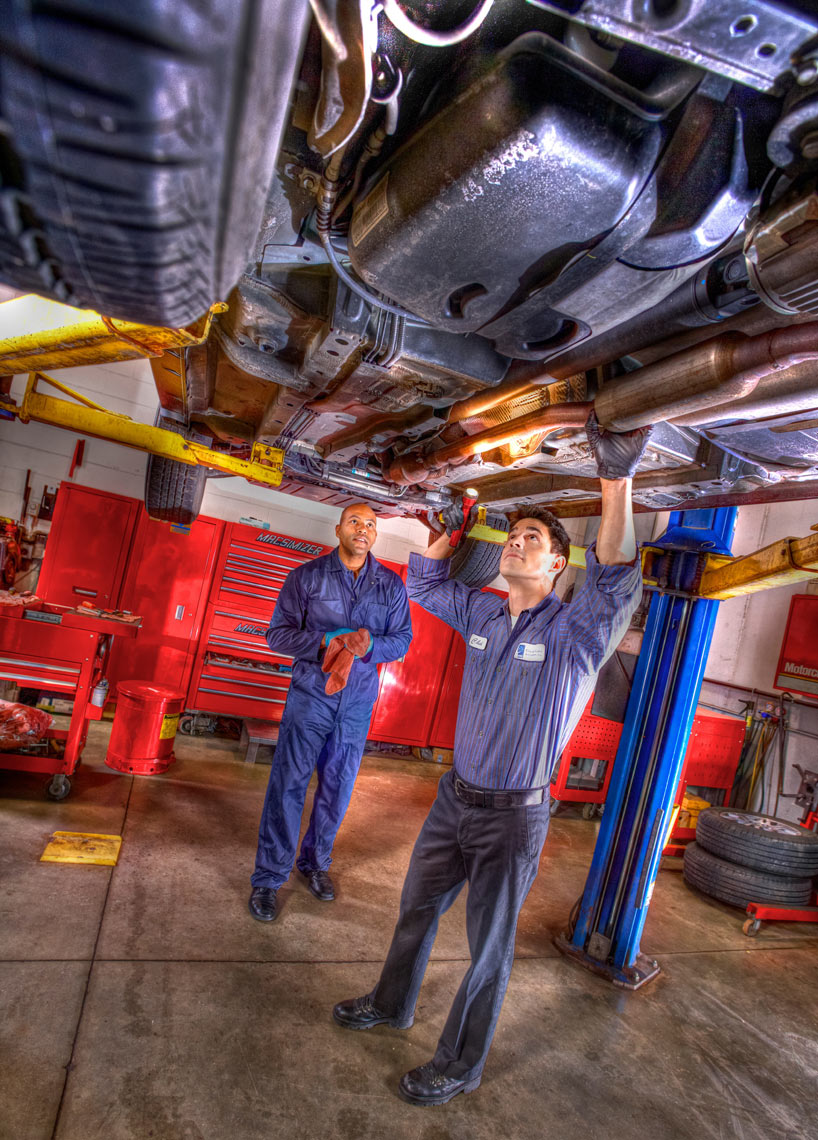 Location Automotive/mechanic working under hoist/location photography