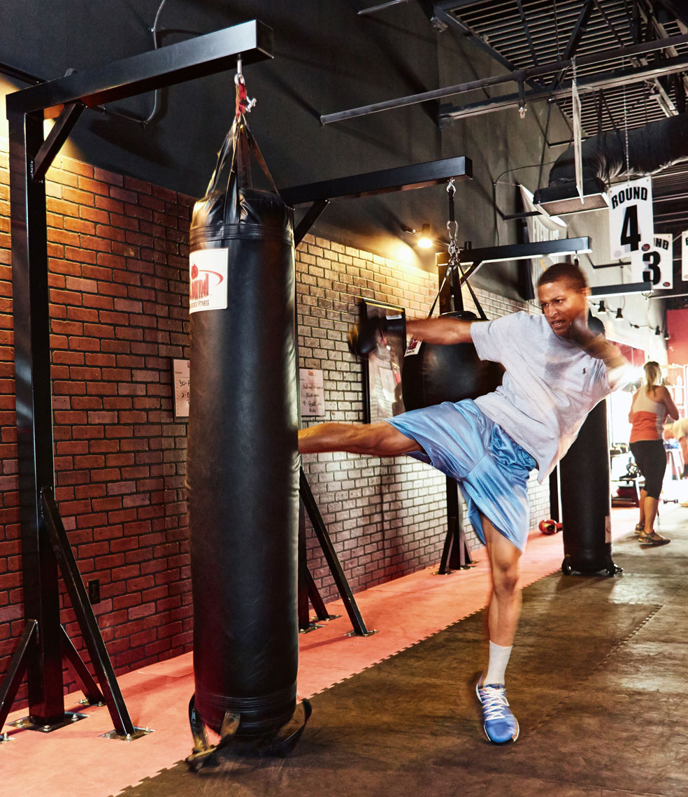 Man kicking body bag/9 Round Fitness/brick wall/lifestyle photography