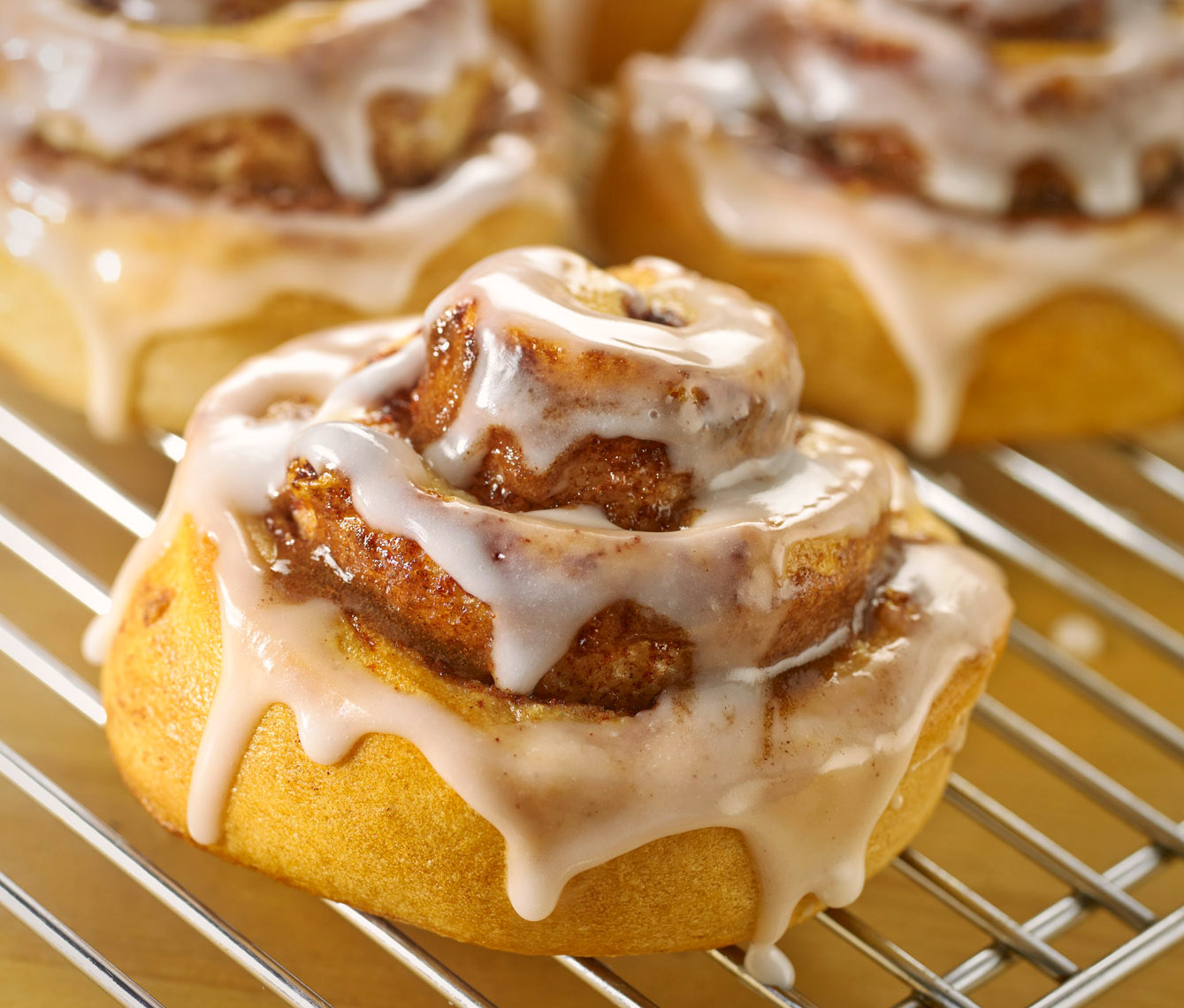 Cinnamon rolls with dripping frosting on a cooling rack. Food photography, InsideOut Studios.