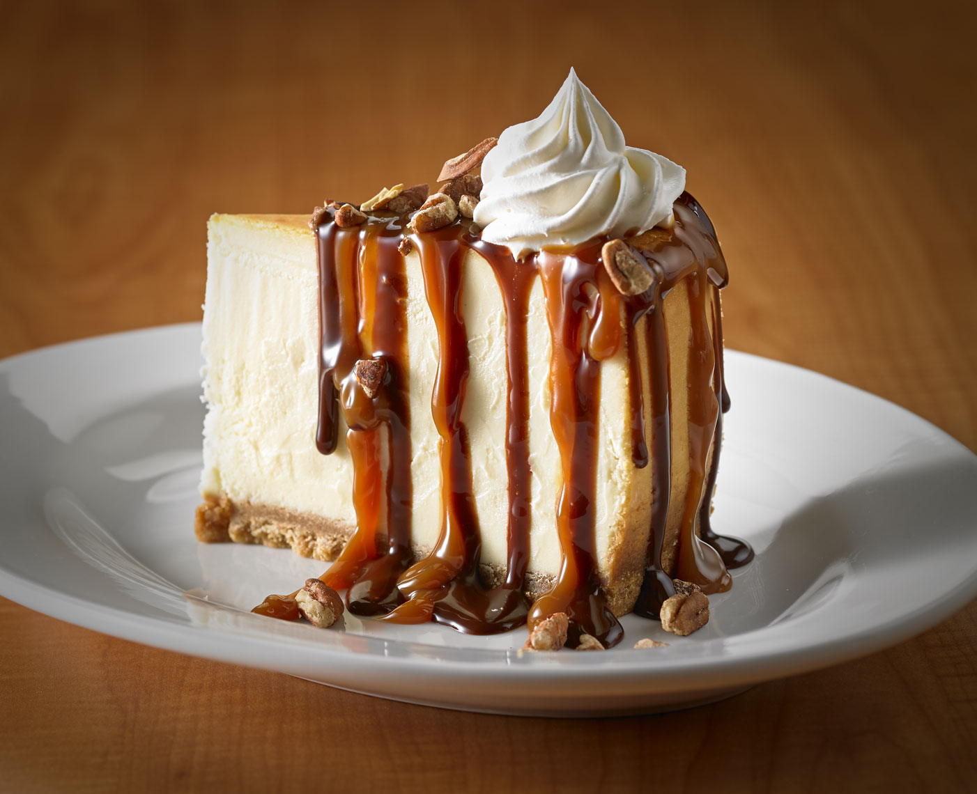Cheesecake/caramel and nuts drizzled/whipped cream