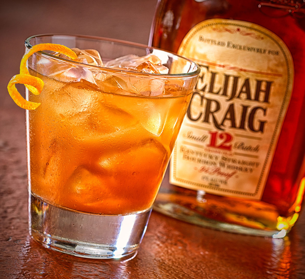 Elijah Craig on the rocks with an orange curl, bottle in background.  Food photography, InsideOut Studios.