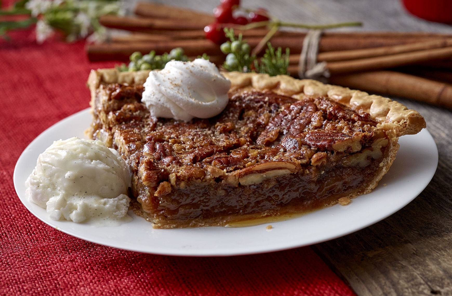 Pecan pie with vanilla ice cream and whipped cream, cinnamon sticks in background.  Food photography, InsideOut Studios.