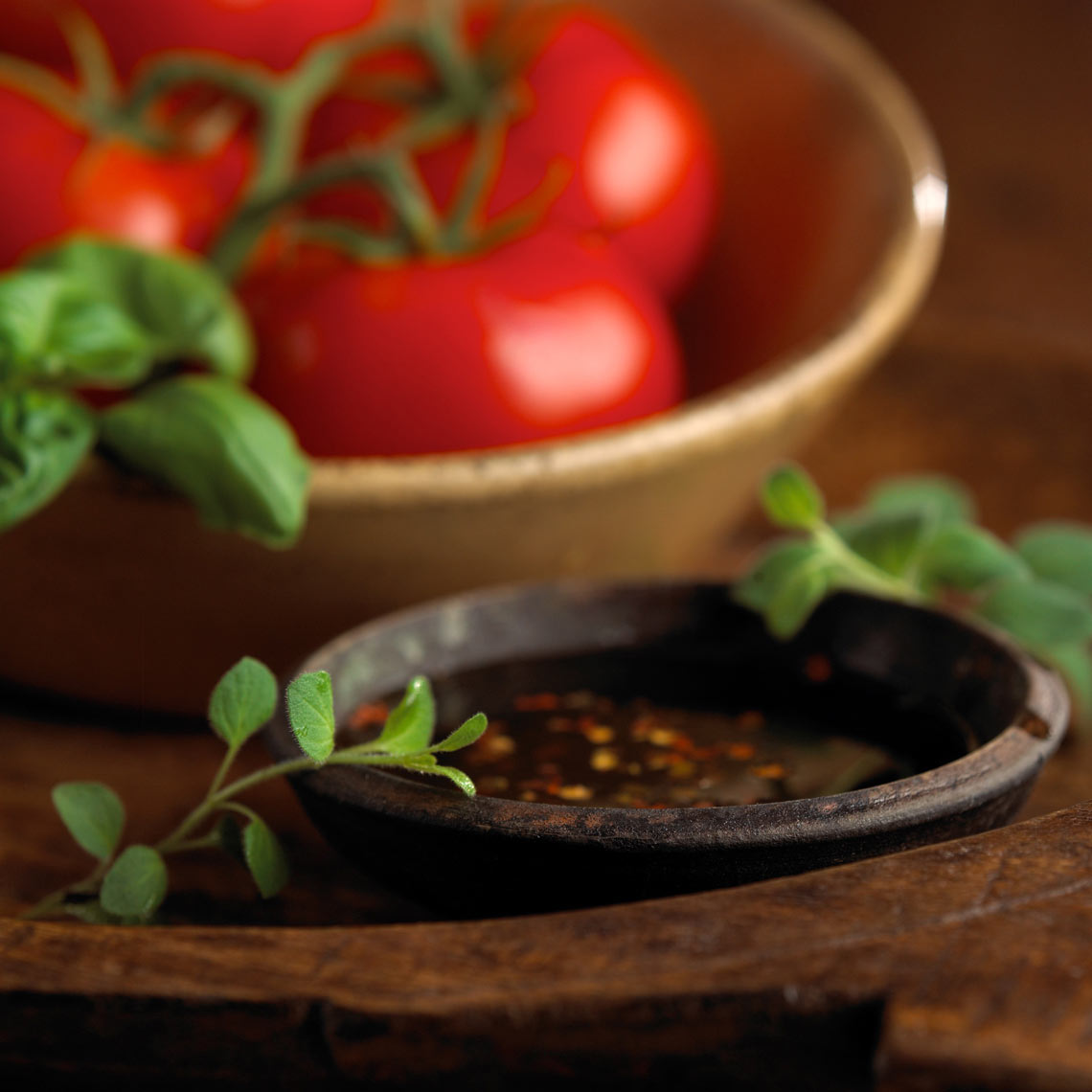 Ramekin of spiced vinaigrette dressing with sprigs of thyme, and bowl of tomatoes Food photography, InsideOut Studios.