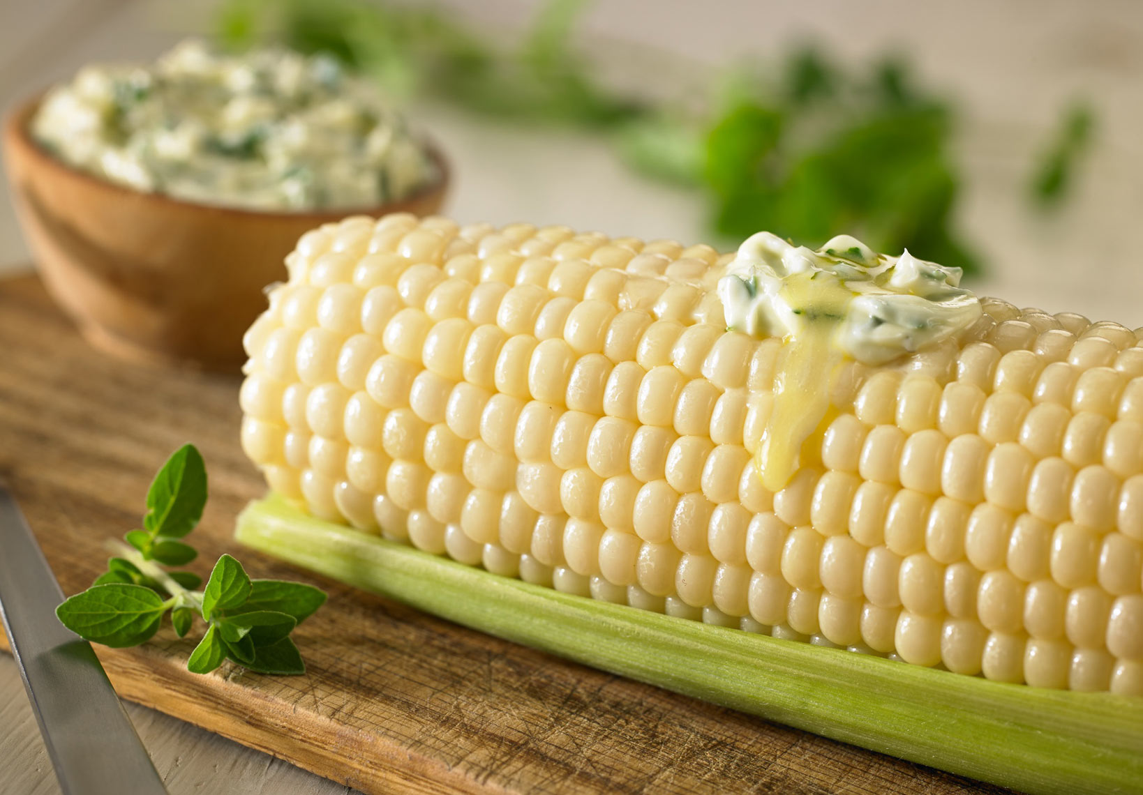 Corn on the cob/herbed butter melting on top/ramekin of herbed butter/food photography, InsideOut Studios