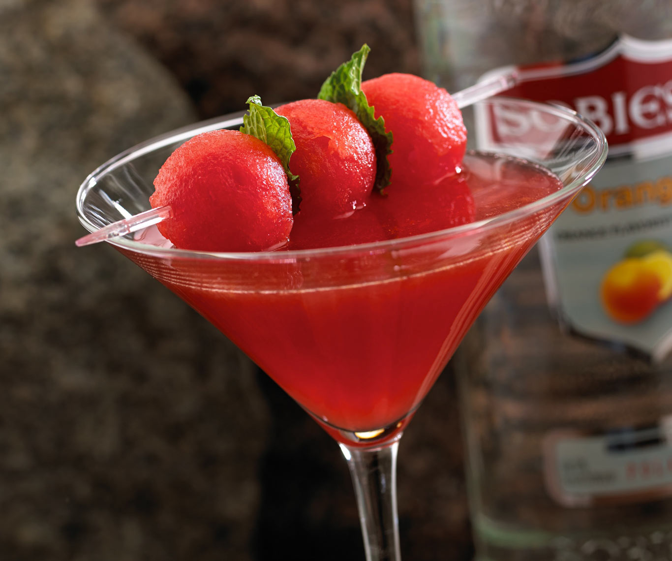 Fruit martini with a skewer of fruit and mint, orange vodka bottle in background.  Food photography, InsideOut Studios.