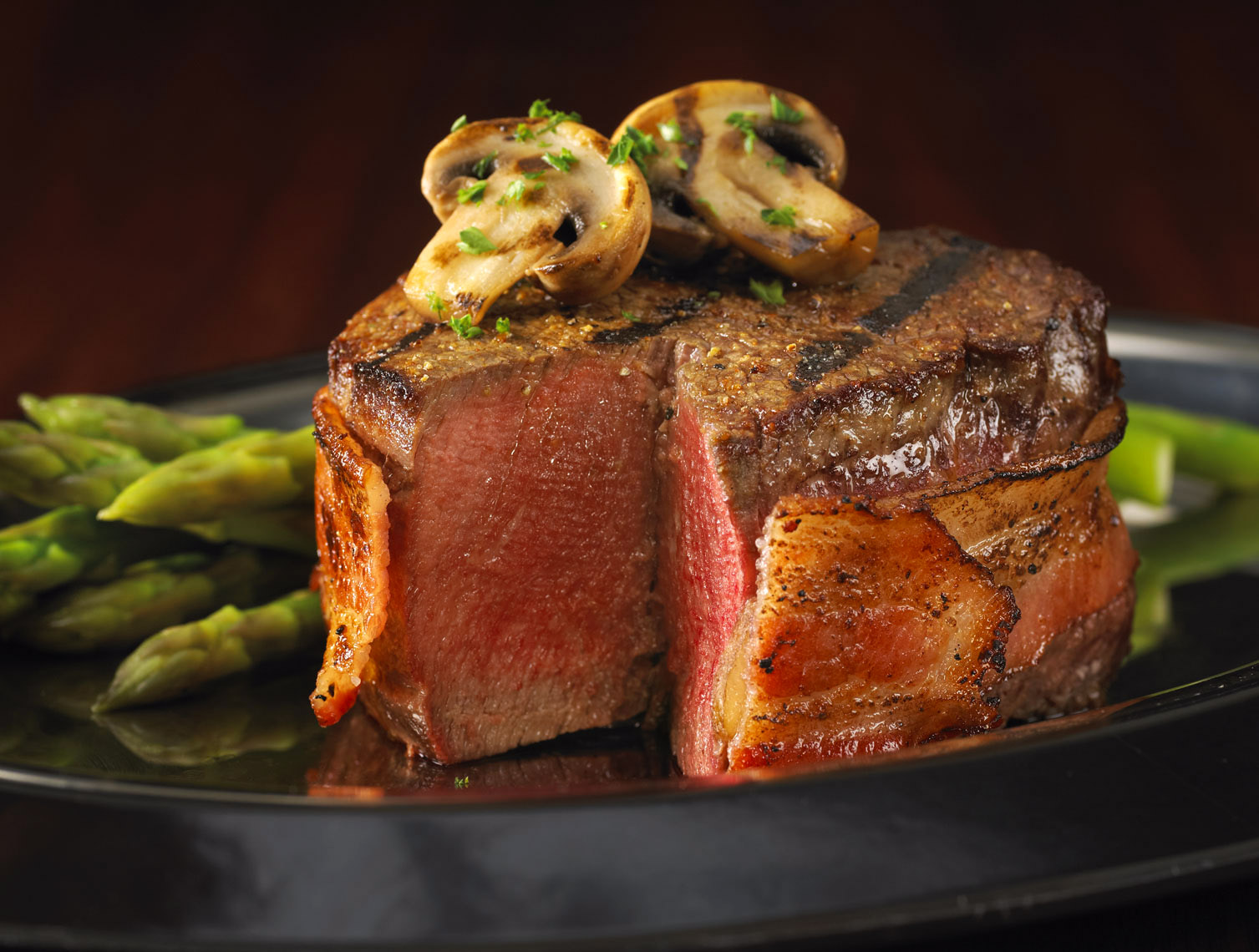 Bacon wrapped steak/slice missing/mushrooms/asparagus on the side/food photography, InsideOut Studios