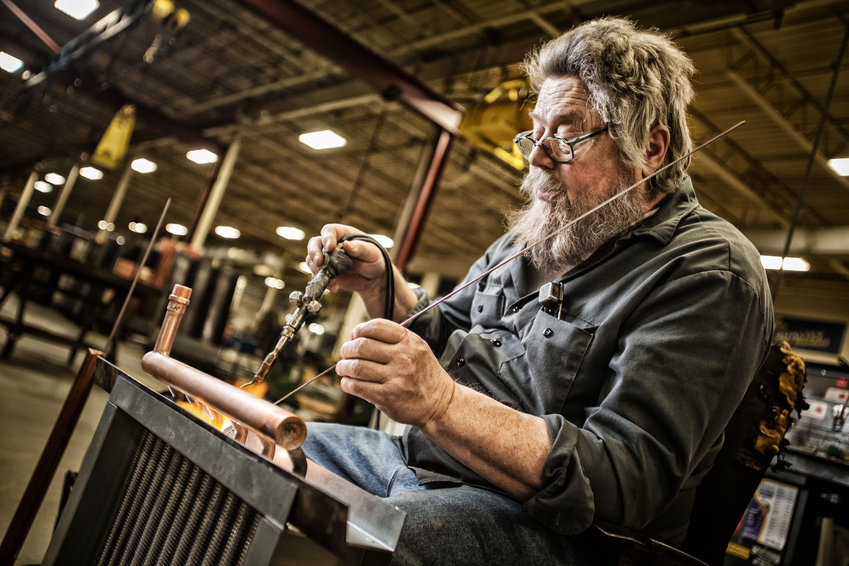 Worker soldering/radiator factory/industrial photography