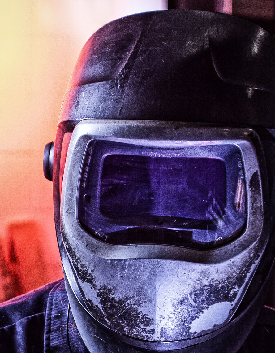 Welder portrait/purple light/close up/industrial photography