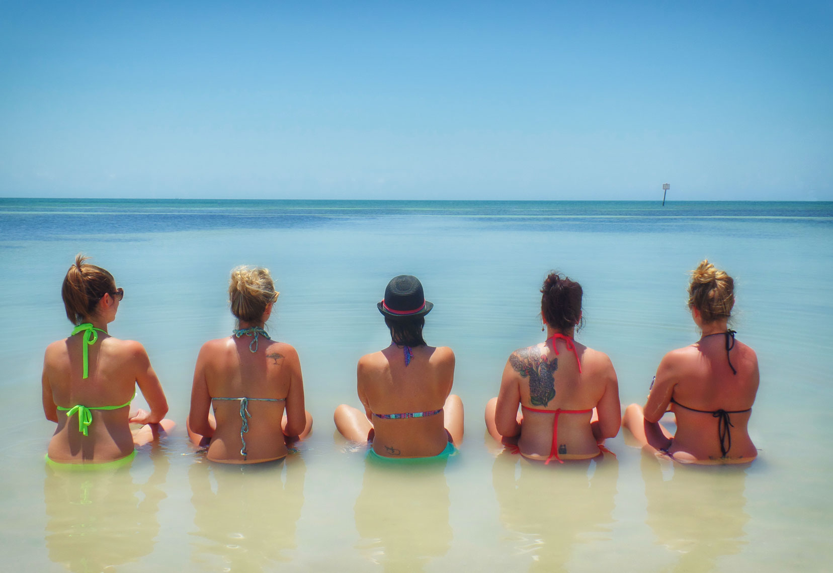 Five women sittinng in ocean/calm water//locaton photography