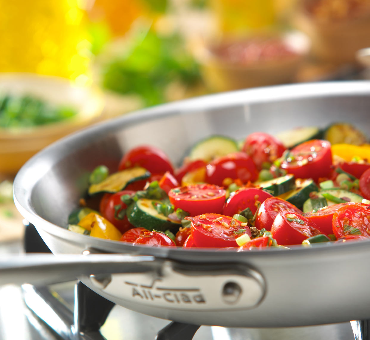 All-Clad skillet with cut tomatoes, zucchini, yellow peppers, and herbs on the stove.  Food photography, InsideOut Studios.