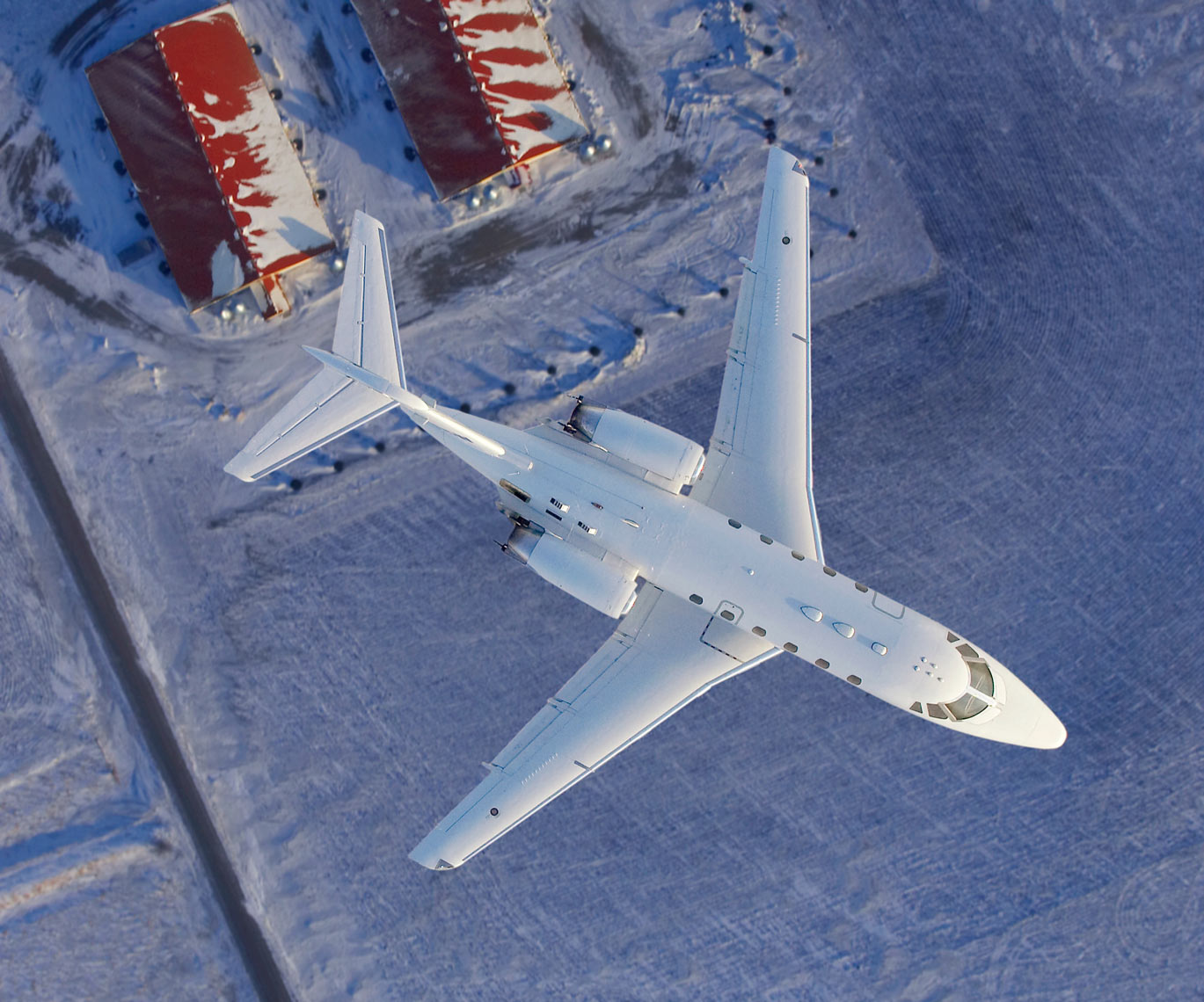 Jet flying over snow field/red barns/aviation photo