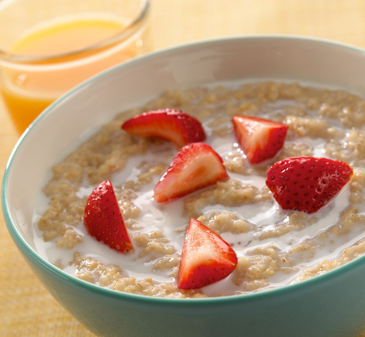 Oatmeal/quartered strawberries/glass of orange juice/food photography