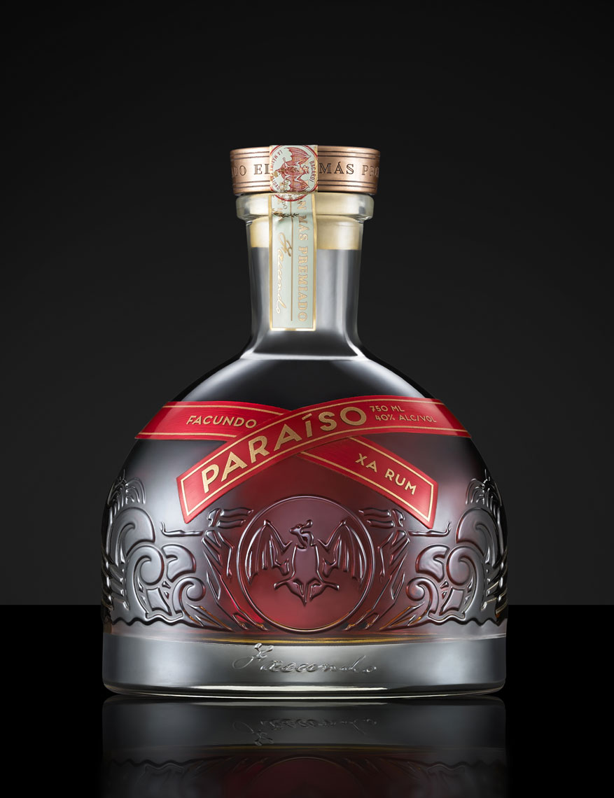 Paraiso rum on black reflective surface with black background; product photography, food photography; InsideOut Studios.