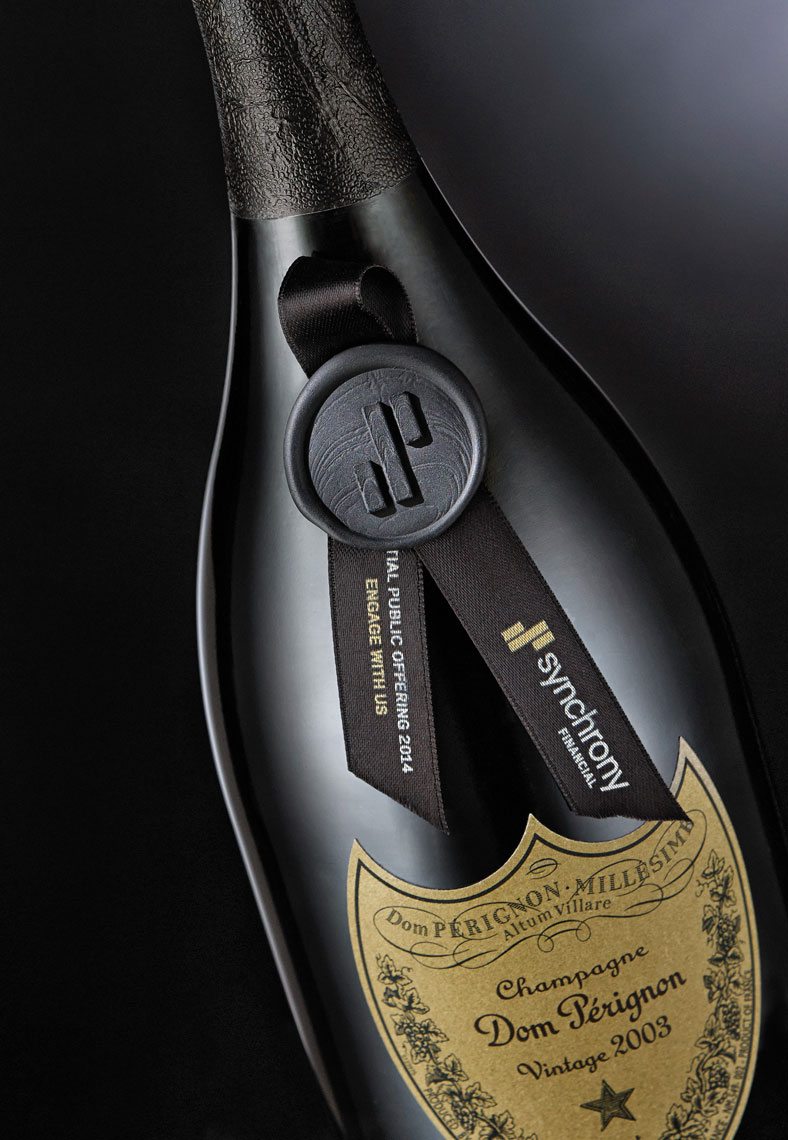 Dom Perignon Champagne bottle with ribbon and seal on black background.  Food photography, InsideOut Studios.