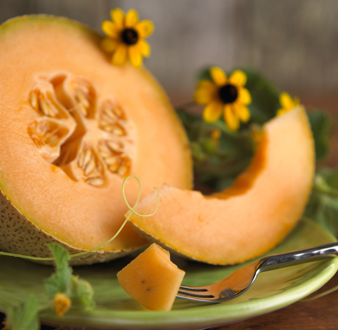 Cantaloupe on a green plate with black eyed Susan's. Food photography, InsideOut Studios.