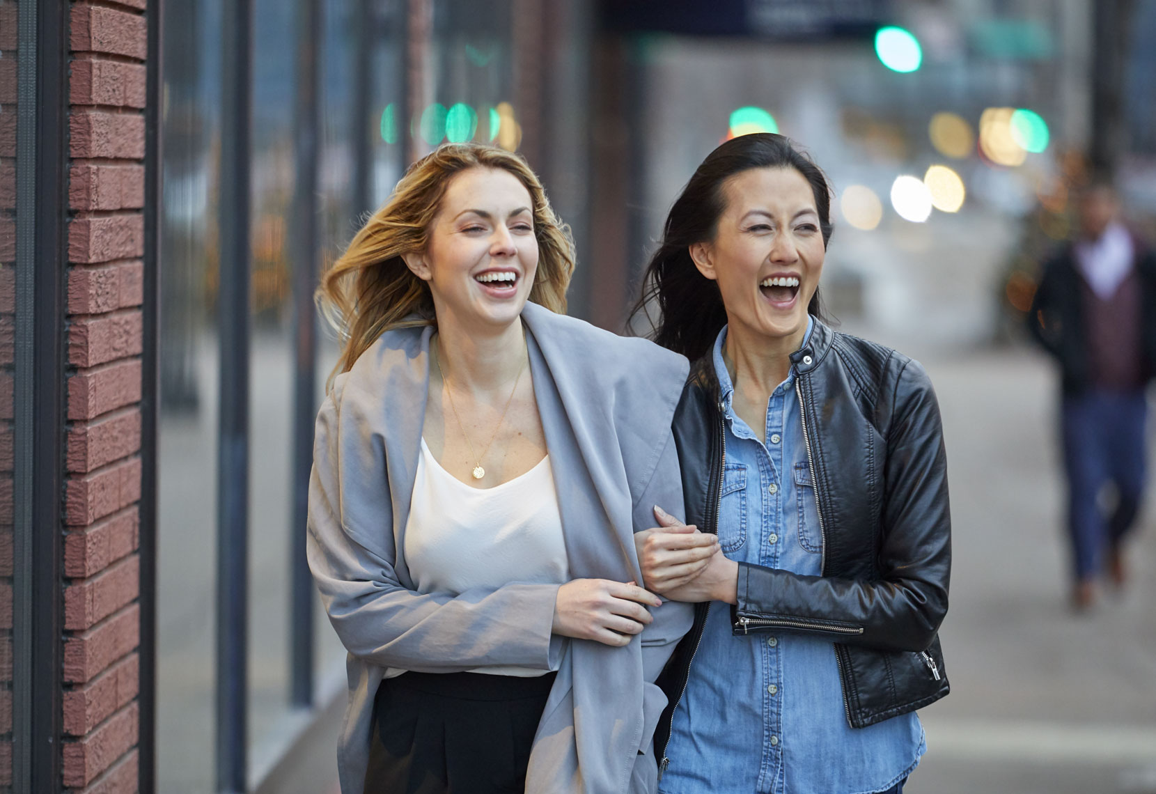 Two women walking/city sidewalk/laughing/lifestyle photography
