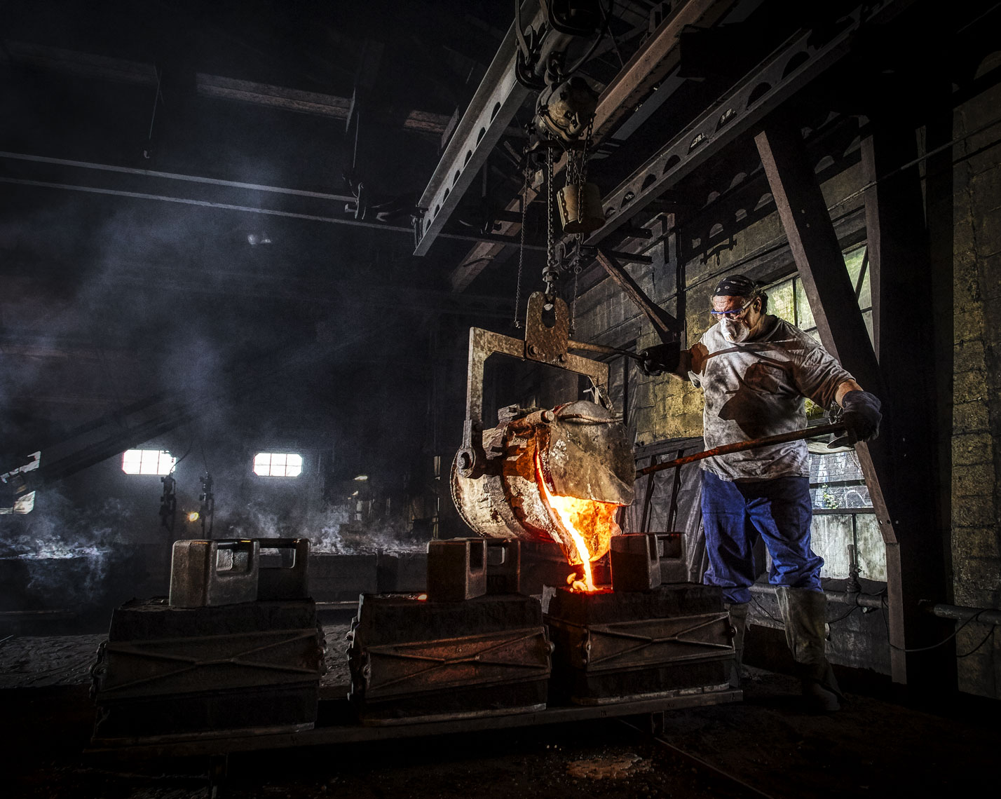 Foundry/liquid metal/worker pouring mold/industrial location photography