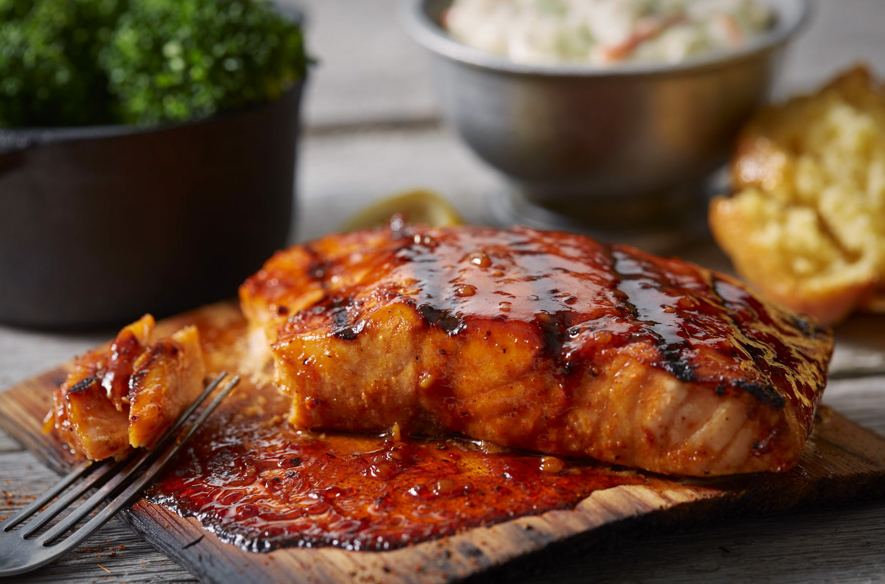 Cedar grilled salmon with glaze.  Various sides in background.  Food photography, InsideOut Studios.