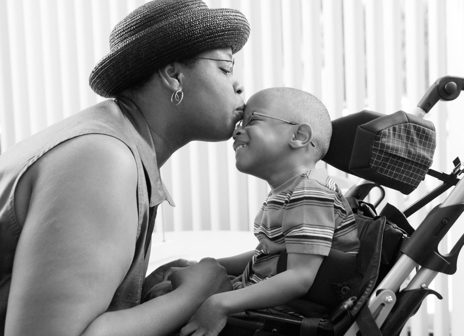 Black mom/kissing child/wheelchair/medical photography